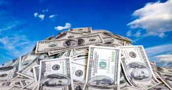 Money piled up with sky background