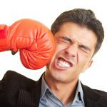 Boxing glove hitting man's face